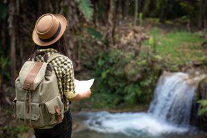 Turismo sostenibile: ragazza che va all'avventura con zaino e cartina, davanti ad una cascata
